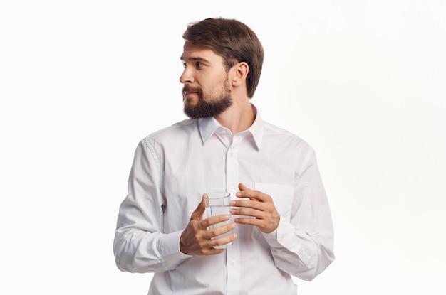 Retrato de un hombre con un vaso de bebida de agua de refrigeración modelo de camisa de fondo claro