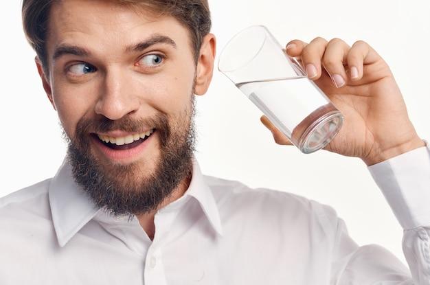 Retrato de un hombre con un vaso de bebida de estilo de vida saludable de agua transparente.