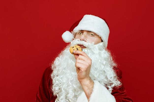Retrato hombre vestido como santa claus comiendo chispas de chocolate