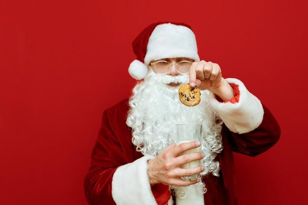 Retrato hombre vestido como santa claus sosteniendo un vaso de leche y un plato con galletas de chocolate