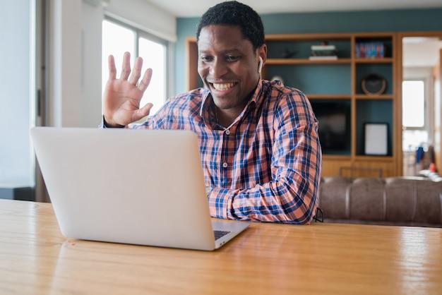 Retrato de hombre en una videollamada de trabajo con ordenador portátil desde casa. concepto de oficina en casa. nuevo estilo de vida normal.