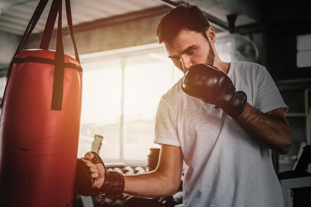 Retrato de hombres deportivos con los guantes de boxeo traseros entrenando en el gimnasio.