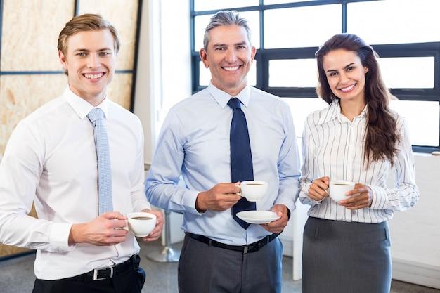 Retrato de hombres de negocios juntos y sonriendo en la oficina durante el recreo