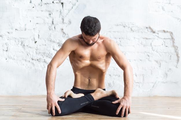 Retrato de hombres yoguis haciendo ejercicios abdominales, respira y practica bloqueo abdominal hacia arriba