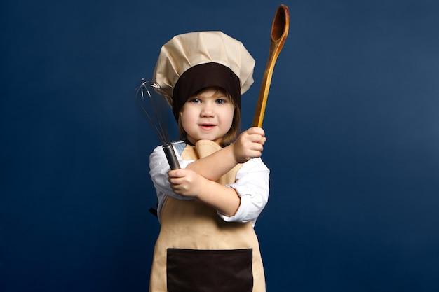 Retrato horizontal de adorable niña caucásica en uniforme de chef cruzando los brazos sosteniendo una cuchara de madera y un batidor, posando sobre fondo de pared de estudio en blanco con espacio de copia para su contenido