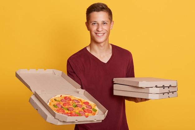 Retrato horizontal de alegre correo carismático mirando directamente, sosteniendo una caja abierta de pizza