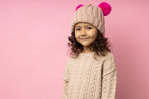 Retrato horizontal de una amigable niña con el pelo rizado, vistiendo un suéter beige, gorro de invierno con pompones peludos carmesí, sonriendo mirando, con espacio de copia. moda infantil.