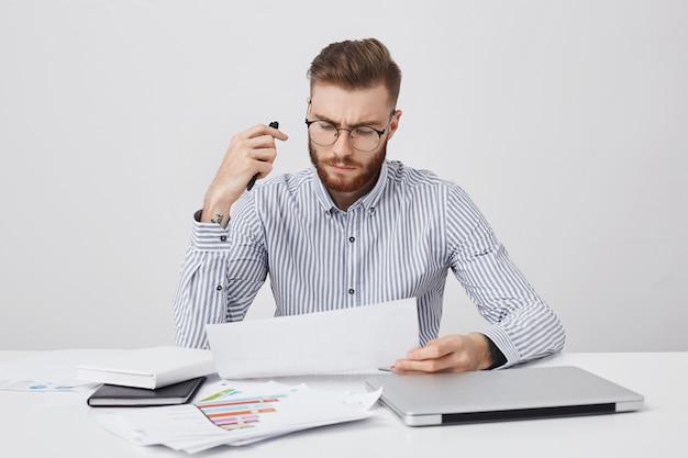 Retrato horizontal del atractivo gerente masculino golpeado, se sienta en la oficina, rodeado con un portátil