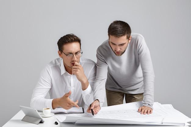 Retrato horizontal de desconcertados trabajadores arquitectos ocupados intentan entender bocetos, apuntar con lápiz,