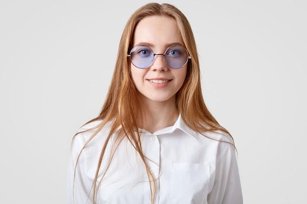 El retrato horizontal de una estudiante alegre viste camisa blanca, tonos redondos de moda, mira directamente a la cámara, modelos en estudio solo