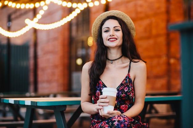Retrato horizontal de hermosa mujer con maquillaje vestido con sombrero de paja y vestido