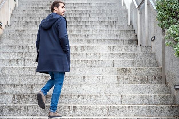 Retrato horizontal del hombre atractivo joven que se coloca en los pasos que miran hacia atrás. chico moderno y elegante tiene las manos del portátil.
