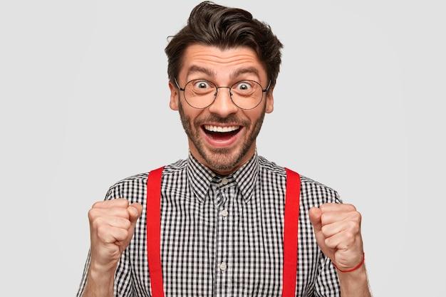 El retrato horizontal de un joven europeo alegre tiene expresión facial llena de alegría, aprieta los puños con entusiasmo, usa camisa a cuadros y tirantes rojos, expresa felicidad después de ganar el concurso