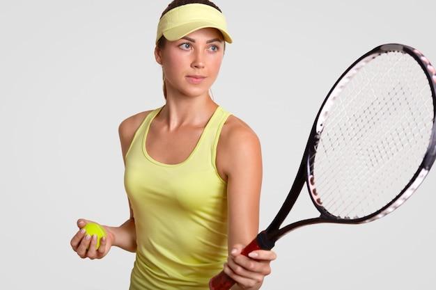 El retrato horizontal del jugador de tenis femenino bastante profesional sostiene la raqueta, lista para hacer su tiro favorito, sostiene la bola
