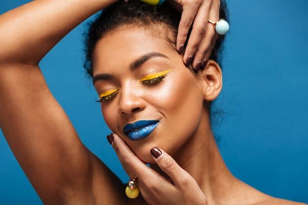 Retrato horizontal de mujer afroamericana relajada con cosméticos coloridos cerrando los ojos y tocando su rostro con las manos aisladas, sobre la pared azul