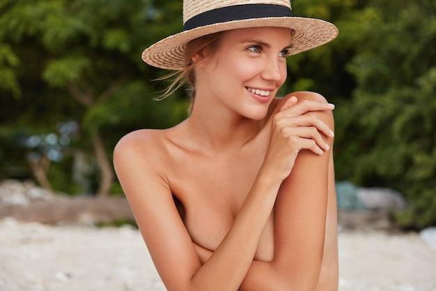 El retrato horizontal de una mujer alegre y pensativa esconde el cuerpo desnudo, muestra una piel suave y saludable y una figura perfecta, usa un sombrero de paja.