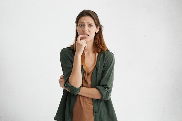 Retrato horizontal de mujer confundida con cálidos ojos oscuros, cabello lacio teñido oscuro y rostro largo sosteniendo su dedo en los dientes teniendo difícil elección frunciendo el ceño sin saber qué elegir