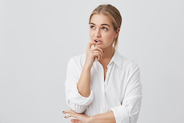 Retrato horizontal de mujer confundida con el pelo liso teñido de rubio, sosteniendo su dedo sobre los dientes haciendo difícil elegir no saber qué elegir.