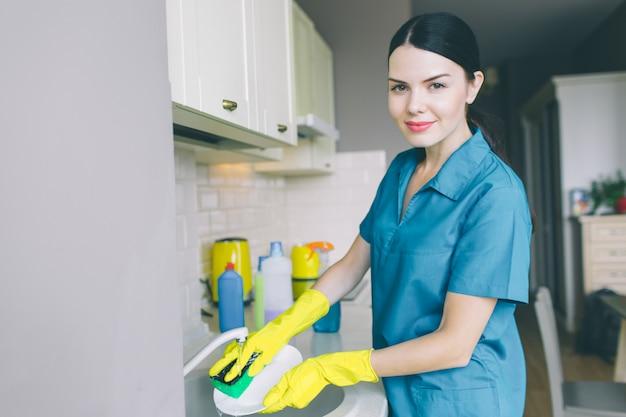 Retrato horizontal de mujer lava platos en el fregadero