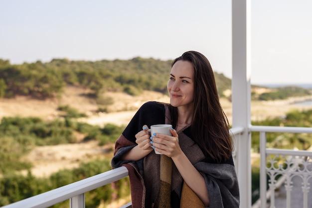 Retrato horizontal de mujer de vacaciones, de pie en la terraza con taza de café