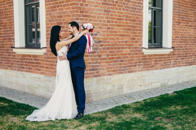 Retrato horizontal de la novia y el novio romántico abrazo como soporte al aire libre cerca de la antigua construcción