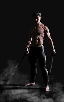 Retrato humano de un guerrero antiguo musculoso guapo con una espada con trazado de recorte