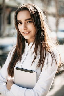 Retrato de una increíble mujer de pelo largo mirando a la cámara confiada mientras sostiene una tableta vestida con camisa blanca afuera en la calle.