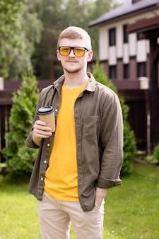 Retrato de independiente joven empresario chico inconformista de pie al aire libre, descansando en el parque con una taza de té, descanso para tomar café, estudiante masculino escalofriante. verano, ocio, tiempo libre, gente, concepto de persona creativa.