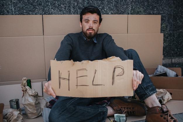 Retrato de indigente sentado en cartón y sosteniendo una ayuda de cartón en las manos