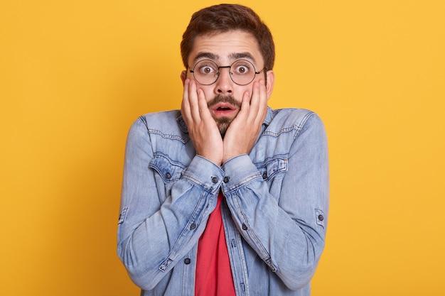 Retrato de un individuo asustado conmocionado emocionalmente que abre los ojos y la boca ampliamente, pone las manos en la cara y ha impresionado la expresión facial