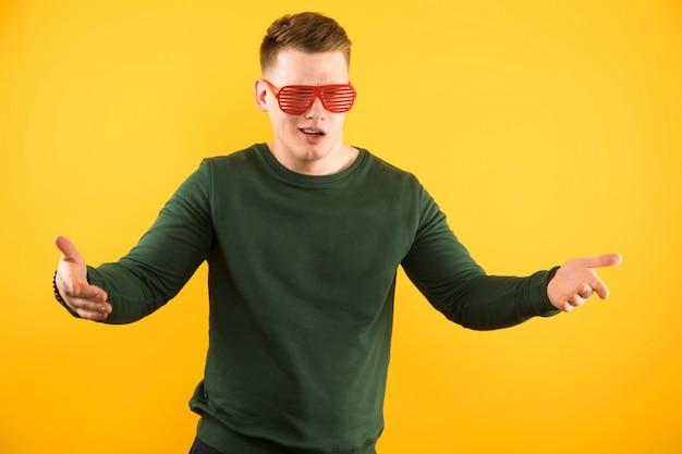 Retrato del individuo sonriente hermoso joven con las gafas de sol que muestran gesto con los brazos abiertos