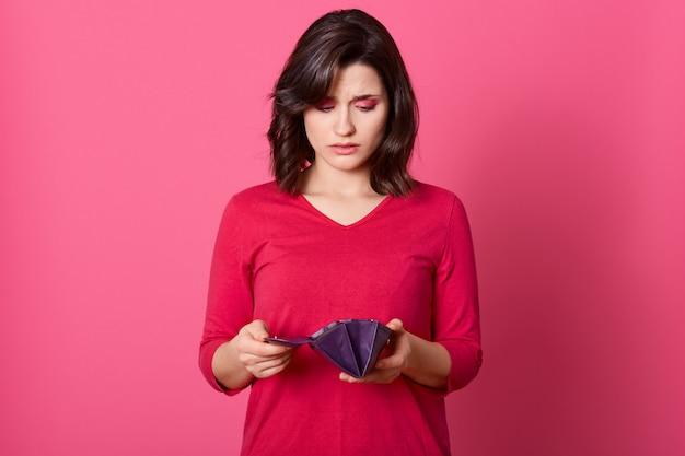 Retrato de infeliz destacó bella dama mirando en billetera vacía abierta con expresión molesta.