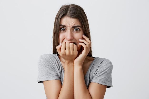Retrato de infeliz joven caucásica apuesta con cabello largo y oscuro en camiseta gris casual royendo los dedos, con expresión de miedo,