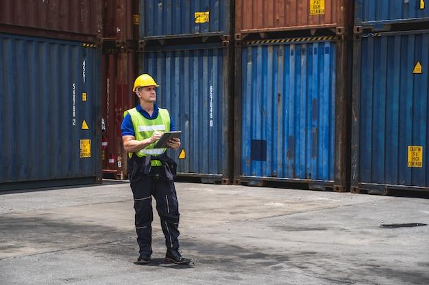 Retrato de ingeniero caminando para comprobar la caja de contenedores