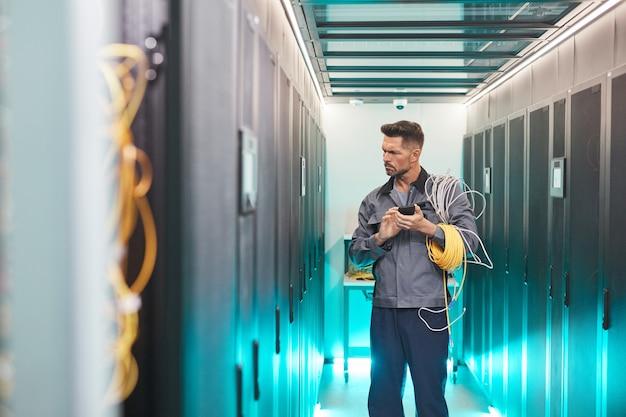Retrato de ingeniero de redes barbudo inspeccionando la sala de servidores en el centro de datos, espacio de copia