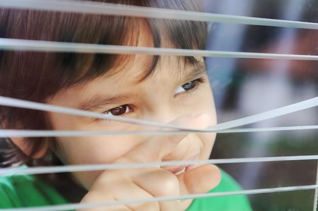 Retrato de un inocente niño pequeño mirando por la ventana con celos