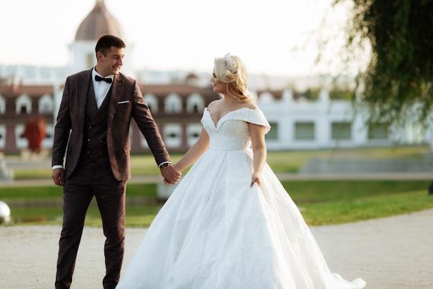 Retrato integral del cuerpo de la novia joven y del novio que se ejecutan en la hierba verde del campo de golf, visión trasera. feliz pareja caminando por el campo de golf, espacio de copia