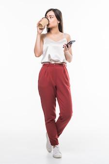 Retrato integral de una empresaria asiática sonriente que usa el teléfono móvil mientras que sostiene la taza de café para ir aislado sobre la pared blanca