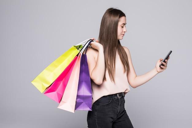 Retrato integral de una mujer joven feliz que sostiene bolsos de compras y el teléfono móvil en una pared blanca