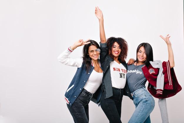 Retrato interior de amigos bastante internacionales divertidos bailando y agitando las manos. adorable chica asiática en jeans pasar el fin de semana con compañeros de la universidad y posando.
