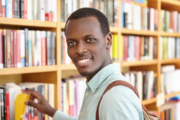 Retrato interior del apuesto hombre africano recogiendo libro de estantería en la librería. estudiante feliz negro pasando vacaciones en la biblioteca de la universidad, tomando prestado un libro de texto para investigación