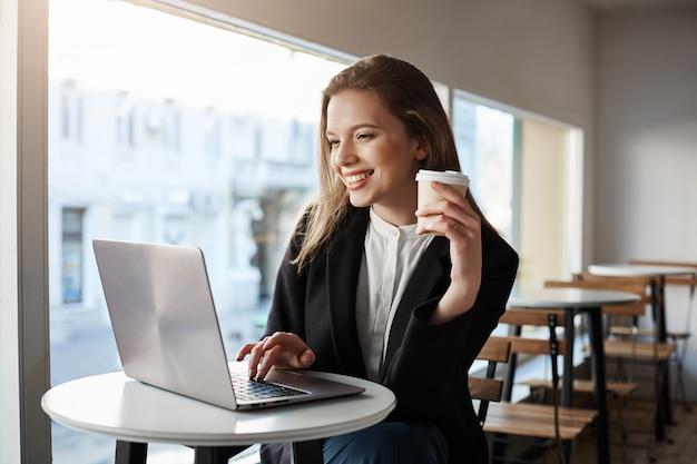 Retrato interior de atractiva mujer europea sentada en la cafetería, tomando café y escribiendo en la computadora portátil, ser feliz y satisfecho.