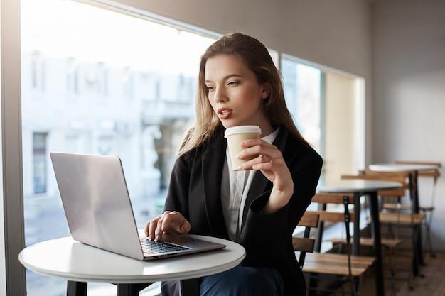 Retrato interior de atractiva mujer europea sentada en la cafetería, tomando café y escribiendo en la computadora portátil