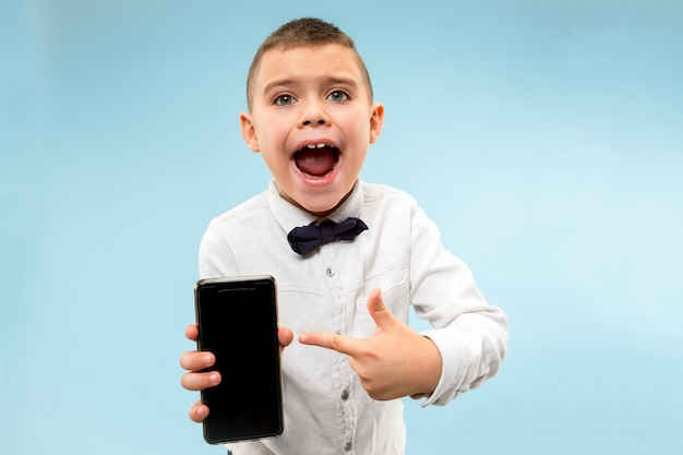 Retrato interior de atractivo joven sosteniendo smartphone en blanco