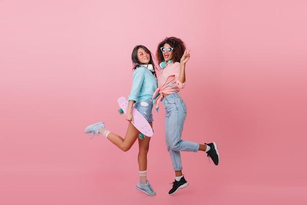 Retrato interior de chicas divertidas bailando con interior rosa. deportiva dama mulata en jeans divirtiéndose con el mejor amigo sosteniendo longboard.