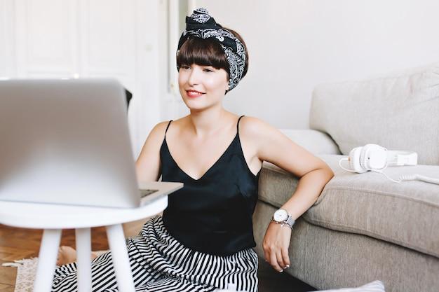 Retrato interior de dama de negocios sonriente trabajando con computadora sentados en el suelo