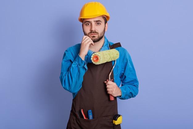 Retrato interior de decepcionado confundido joven constructor poniendo la mano en el mentón, sosteniendo el rodillo, teniendo expresión facial pensativa, vistiendo uniforme y casco, posando aislado sobre la pared de color lila.