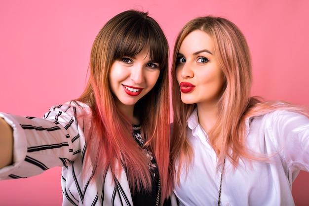 Retrato interior de dos felices mejores amigas hermanas mujeres, vistiendo ropa de moda en blanco y negro y pelos rosados, haciendo selfie, disfrutando del tiempo juntos