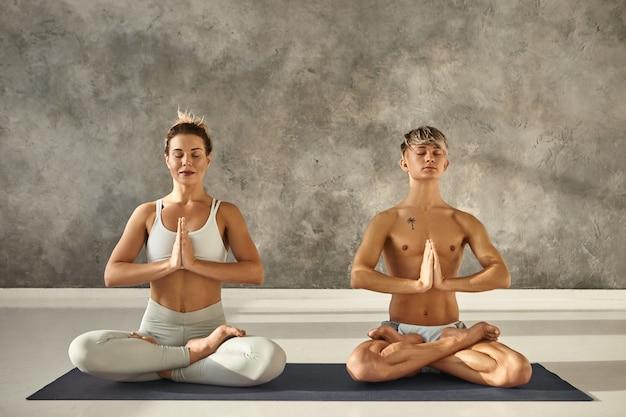 Retrato interior de dos jóvenes descalzos, hombre y mujer con cuerpos fuertes y flexibles, meditando en una colchoneta durante la clase de yoga, sentados en postura de loto, cerrando los ojos y tomados de la mano en namaste