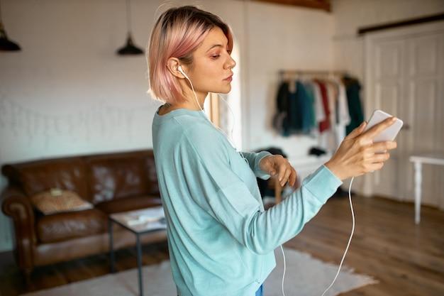 Retrato interior de una elegante adolescente con peinado bob rosa disfrutando de un rato agradable en casa, sosteniendo un teléfono inteligente